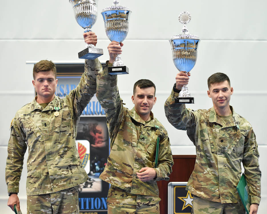 U.S. Army 1st Lt. Kendall Ward (from left to right) of the 173rd Infantry Brigade Combat Team (Airborne), the 2016 European Best Officer Warrior; Staff Sgt. Ethan Rodgers of the 7th Army Training Command, the 2016 Best NCO Warrior; and Spc. Daniel Guenther, also with the 7th ATC, the 2016 Best Soldier Warrior, receive trophies during a concluding ceremony held August 11, 2016 at the Grafenwoehr Physical Fitness Center. (U.S. Army Photo by Visual Information Specialist Gertrud Zach)