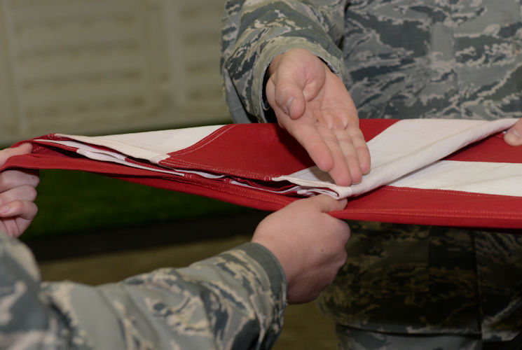 October 26, 2017 - Airman 1st Class Joseph Serrano, a material management specialist assigned to the 28th Logistics Readiness Squadron, presents the first fold of a flag during an honor sequence at the Pride Hangar at Ellsworth Air Force Base, South Dakota. The flag folding sequence entails the march-up formation, the casket carry and the flag fold itself which takes place before or after the eulogy is given. (U.S. Air Force photo by Airman Nicolas Z. Erwin)