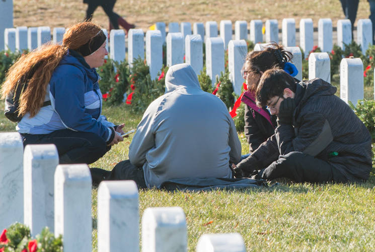 December 16, 2017 - A family of a fallen Soldier sits next to his headstone in Arlington National Cemetery, VA. More than 200,000 wreaths were placed on headstones as part of the annual Wreaths Across America event, which honors the sacrifices made by military members. (Image created by USA Patriotism! from U.S. Army photo by Sean Kimmons)