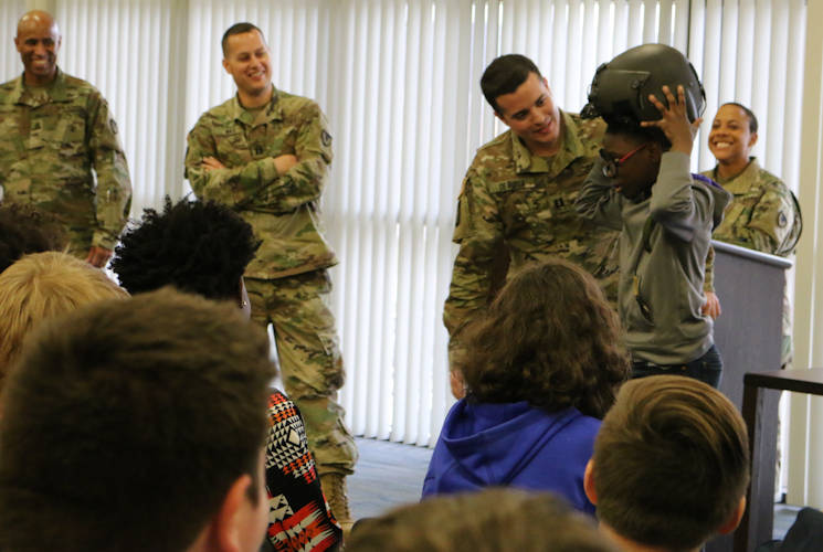 November 8, 2017 - A Buckhorn Middle School student tries on Capt. Alexander De Rosa's pilots helmet during a presentation to seventh and eighth graders at the school. In the background are, from left, Sgt. Maj. Jon Martin, Capt. Justin Wax and 1st Sgt. Lachelle Wiggins. (U.S. Army photo by Kari Hawkins, Aviation & Missile Command)