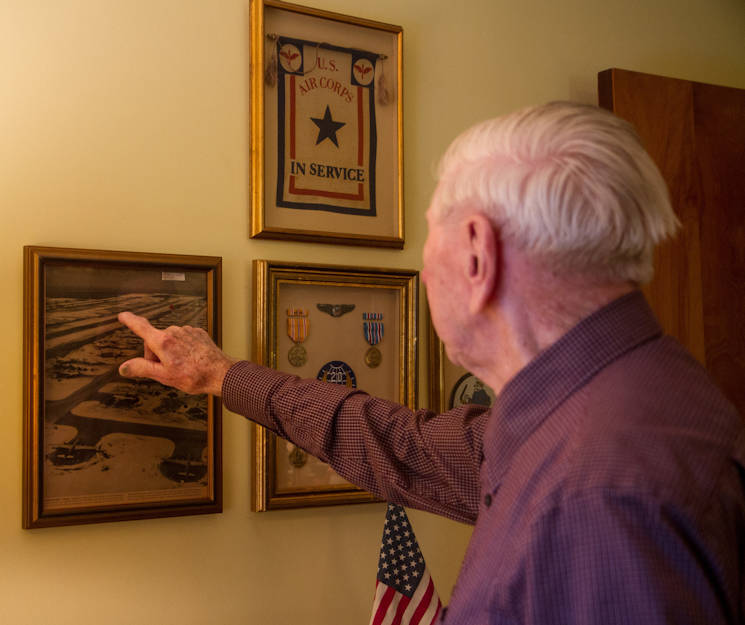 World War II veteran William Dellinger (96) points to the B29 aircraft that he primarily used in the war. The photo of this proud memory hangs on a wall of his home in Charlotte, North Carolina.  Dellinger's medals and ribbons achieved during his service are next to the photo. (U.S. Army photo by Spc. Tynisha Daniel)
