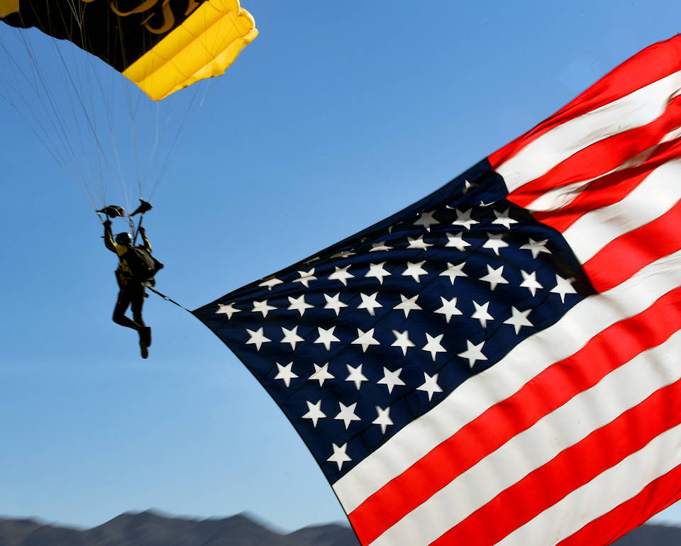 November 16, 2019 - A member of the Para-Commandos, the U.S. Special Operations Command, premier aerial parachute demonstration team carries the American flag as the national anthem plays at the Aviation Nation 2019 Air Show at Nellis Air Force Base, Nevada. (Image created by USA Patriotism! from U.S. Air Force photo by Senior Airman Kevin Tanenbaum)