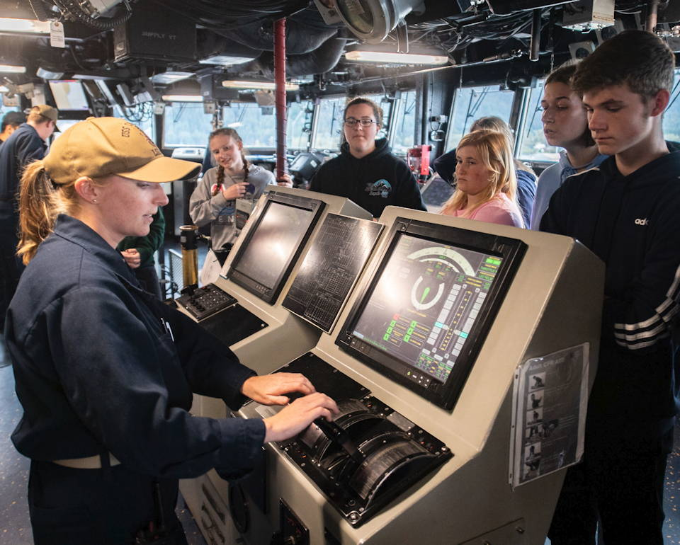 September 19, 2019 -  U.S. Navy Lt. j.g. Kathryn Susko, assigned to the amphibious dock landing ship USS Comstock (LSD 45), demonstrates the roles of the helmsman to Seward High School engineering students during a tour as part of Arctic Expeditionary Capabilities Exercise (AECE) 2019. (Image created by USA Patriotism! from U.S. Navy photo by Mass Communication Specialist 2nd Class Nicholas Burgains)
