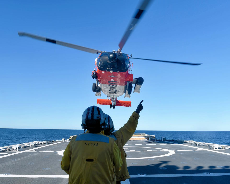 December 27, 2020 - Crew members of the U.S. Coast Guard Cutter Stone (WMSL 758) guide a U.S. Coast Guard MH-60 Jayhawk helicopter to land on the Stone's flight deck off the coast of Florida. The helicopter crew performed multiple training operations with the crew of the Stone. (U.S. Coast Guard photo by Petty Officer 3rd Class John Hightower)