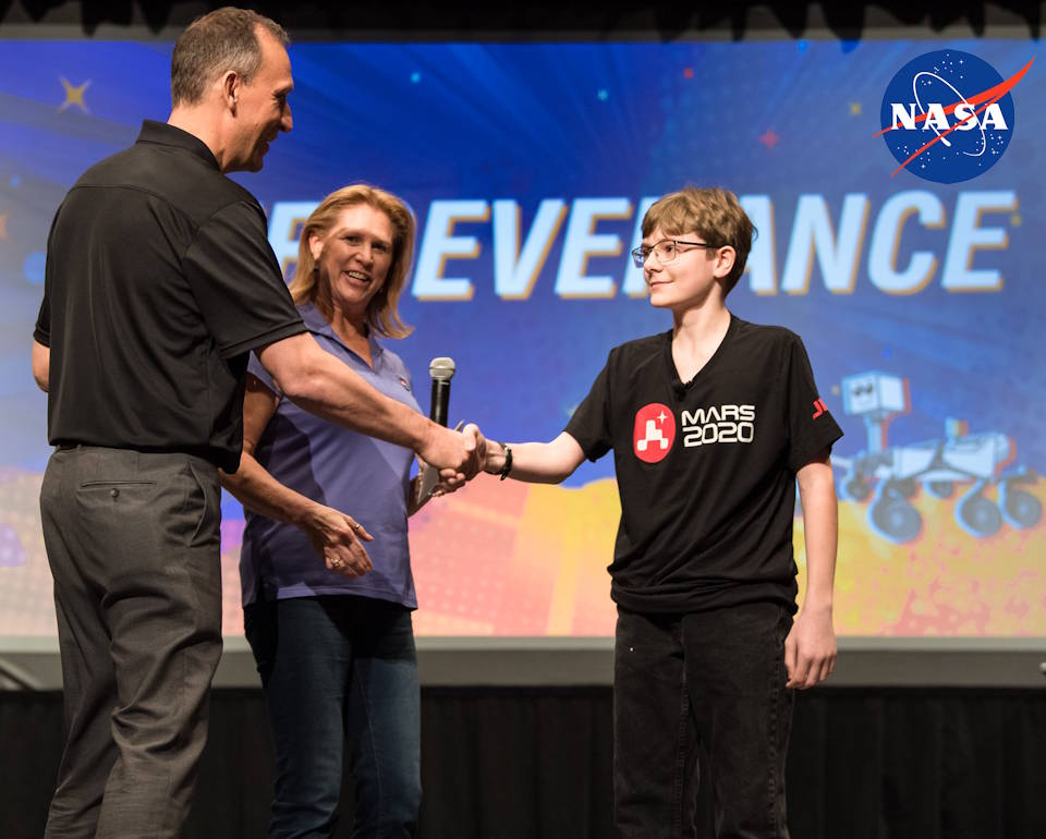 March 5, 2020 - Associate Administrator of NASA's Science Mission Directorate, Thomas Zurbuchen, shakes hands with 13 year-old 7th grader Alex Mather, whose submission of Perseverance was chosen as the official name of the Mars 2020 rover at Lake Braddock Secondary School in Burke, Virginia. (Image created by USA Patriotism! from NASA photo by Aubrey Gemignani)