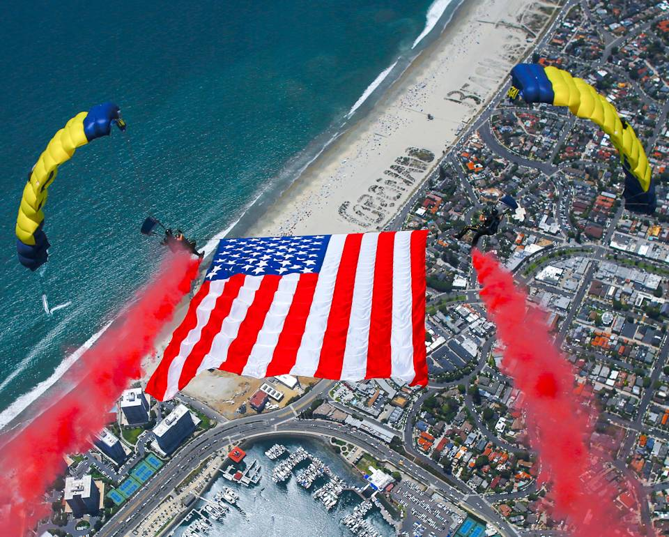 July 4, 2020 - Members of the U.S. Navy parachute team, the Leap Frogs, perform a tethered flag with smoke brackets during a demonstration jump on Independence Day. The Leap Frogs are based in San Diego and perform aerial parachute demonstrations around the nation in support of Naval Special Warfare and Navy recruiting. (Image created by USA Patriotism! from U.S. Navy photo by James Woods)
