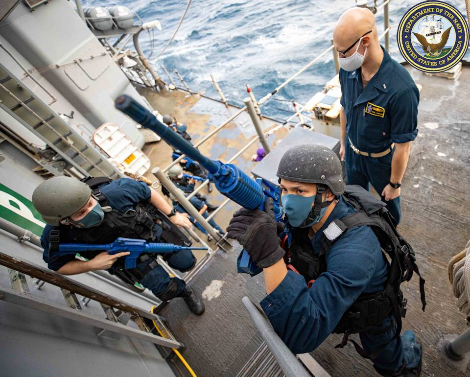 November 13, 2020 - Fire Controlman 1st Class Jonathan Deconte (center) and Fire Controlman 2nd Class Bryce Lemmon (left) secure the starboard boat deck of the Ticonderoga-class guided-missile cruiser USS Shiloh (CG 67) as Lt. j.g. Tyler Hagedorn (right) observes as safety during a visit, board, search and seizure exercise. (Image created by USA Patriotism! from U.S. Navy photo by Mass Communication Specialist 2nd Class Ryre Arciaga.)