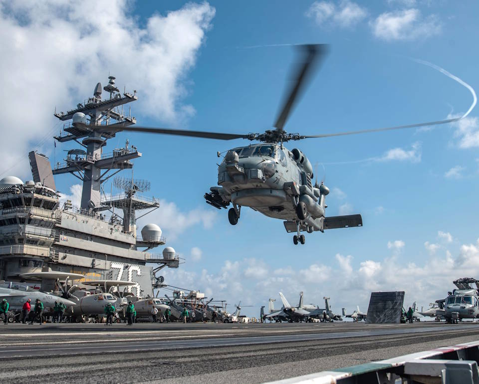 July 28, 2020 - An MH-60R Sea Hawk attached to the Saberhawks of Helicopter Maritime Attack Squadron (HSM) 77 lifts off the flight deck of the Navy's only forward-deployed aircraft carrier USS Ronald Reagan (CVN 76). (Image created by USA Patriotism! from U.S. Navy photo by Mass Communication Specialist 2nd Class Samantha Jetzer)