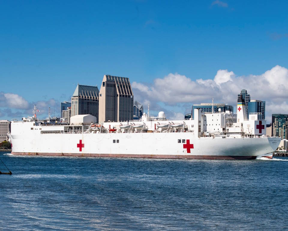 March 23, 2020) -- Military Sealift Command hospital ship USNS Mercy (T-AH 19) navigates the San Diego channel. Mercy deployed in support of the nation's COVID-19 response efforts, and will serve as a referral hospital for non-COVID-19 patients currently admitted to shore-based hospitals. This allows shore base hospitals to focus their efforts on COVID-19 cases. (Image created by USA Patriotism! from U.S. Navy photo by Mass Communication Specialist 3rd Class Lasheba James)