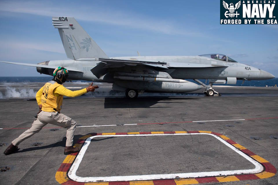 "February 12, 2021 – U.S. Navy Lt. Travis Boller signals the launch of an an F/A-18E Super Hornet, assigned to the ""Golden Warriors"" of Strike Fighter Squadron (VFA) 87, on the flight deck of the aircraft carrier USS Theodore Roosevelt (CVN 71). (Image created by USA Patriotism! from U.S. Navy photo by Mass Communication Specialist Seaman Faith McCollum.)"