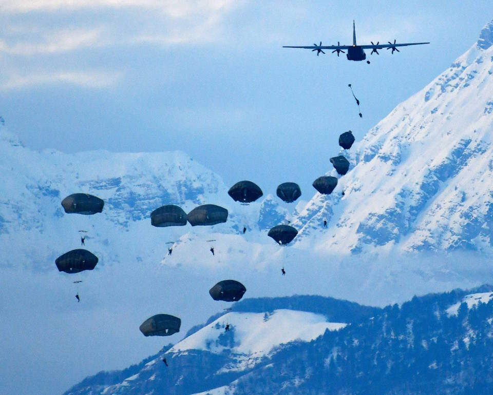 February. 1, 2021 - U.S. Army Paratroopers assigned to the 173rd Airborne Brigade, conduct an airborne operation after exiting a U.S. Air Force 86th Air Wing C-130 Hercules aircraft at Frida Drop Zone, Pordenone, Italy with snow covered mountains in the background. The 173rd Airborne Brigade is the U.S. Army Contingency Response Force in Europe, capable of projecting ready forces anywhere in the U.S. European, Africa or Central Commands' areas of responsibility. (Image created by USA Patriotism! from U.S. Army photo by Paolo Bovo.)