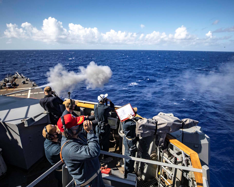 March 16, 2021 - Cmdr. Tin Tran, commanding officer of the Arleigh Burke-class guided-missile destroyer USS John S. McCain (DDG 56), Capt. Chase Sargeant, commodore of Destroyer Squadron (DESRON) 15, and other crewmembers observe as John S. McCain's 5-inch gun fires at an unmanned aerial vehicle during a counter unmanned aerial strike training exercise. (Image created by USA Patriotism! from U.S. Navy photo by Mass Communication Specialist 1st Class Jeremy Graham.)