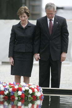 President George W. Bush and Laura Bush stand in silence after laying a wreath in the north reflecting pool at Ground Zero September 10, 2006, in commemoration of the fifth anniversary of the terrorist attacks of September 11, 2001, on the World Trade Center in New York City.