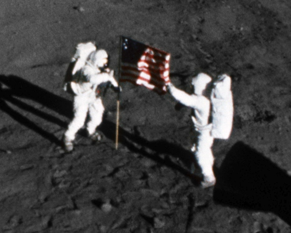 "The deployment of the flag of the United States on the surface of the moon is captured on film on July 20, 1969, during the first Apollo 11 lunar landing mission. Astronaut Neil A. Armstrong, commander, stands on the left at the flag's staff. Astronaut Edwin E. ""Buzz"" Aldrin Jr., lunar module pilot, is pictured on the right. The picture was taken from film exposed by the 16mm Data Acquisition Camera which was mounted in the Lunar Module. (NASA courtesy photo)"