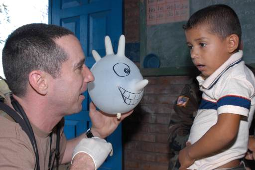U.S. Navy Lt. William Jansak uses a balloon made from a rubber glove to ease the fears of a young patient in Nicaragua.