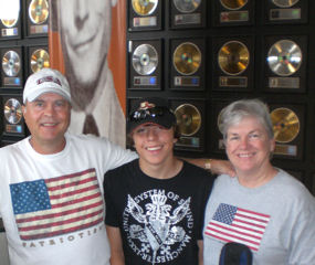 David Bancroft (founder of USA Patriotism!) with wife and grandson in front large wall display of the gold and platinum records of various artists at the Country Music Hall of Fame and Museum.
