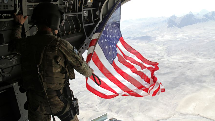 U.S Army Sgt. Michael Misheff, CH-47F Chinook helicopter chew chief for Task Force Flying Dragons, flies the American flag over southern Afghanistan Aug. 28, 2014. Task Force Raptor pilots and crew chiefs fly American flags to present with certificates to service members as part of aviation tradition. (U.S Army photo by Staff Sgt. Bryan Lewis)