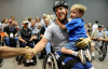 Sean Halsted shakes hands with a fan as he holds his son, Ethan, 5, after completing the slalom super G competition during the 29th National Veterans Wheelchair Games July 16, 2009 in Spokane, Wash. Mr. Halsted is an Air Force veteran and resides in Rathdrum, Idaho.