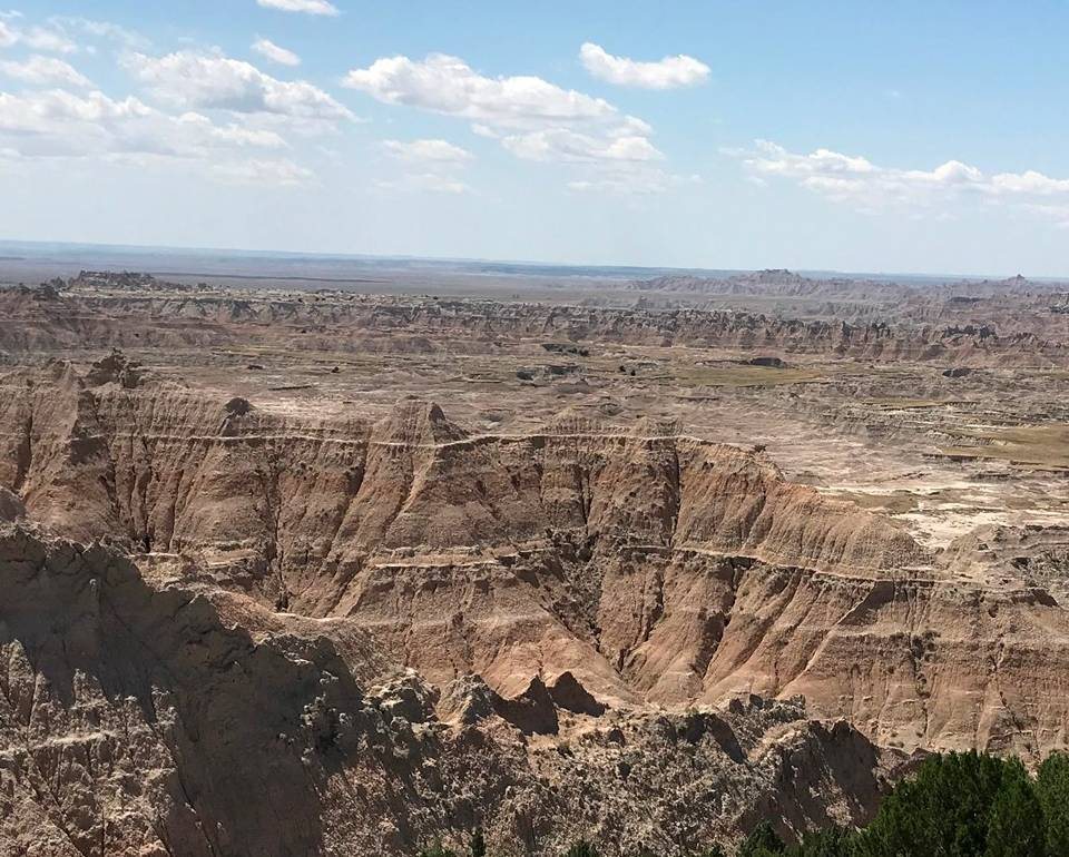 The Pinnacles Overlook within Badlands National Park located in South Dakota has sweeping views facing South ... as shown in this scenic view of Sage Creek Wilderness area and beyond. (Image created by USA Patriotism! from U.S. National Park Service photo by Serena Rosales.)